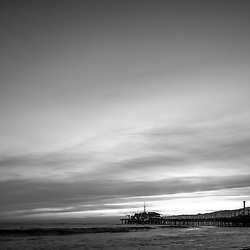 Santa Monica Pier at sunset black and white picture along the Pacific Ocean in Southern California. Copyright ⓒ 2017 Paul Velgos with All Rights Reserved.