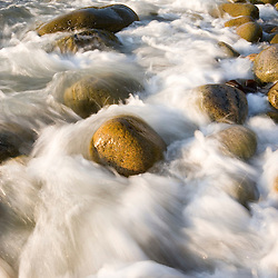 Waves wash over the cobblestones in Monument Cove in Maine's Acadia National park. Mount Desert Island.