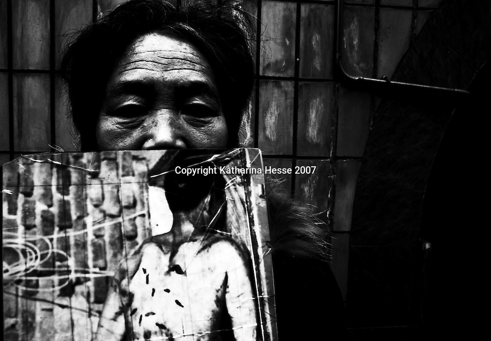 BEIJING, DECEMBER 26, 2007. A mother from Shijazhuang in Hebei Province in China, holds a photo of her son, who was stabbed to death in 2003. The murderer was found not guilty by the court. For 3 years this woman has been coming to Beijing trying to file a complaint in order to reverse the verdict... In the past decades, hundreds of thousands of Chinese from the provinces have descended upon Beijing in hopes of attracting attention from higher authorities regarding their civil law cases. These cases vary from work accidents, violence against family members, murder, extortion, and the majority of which stem from a corrupt rural legal system...The tradition of petitioning to higher authorities in the Chinese capital reaches back to Imperial times. Outside the city center of Beijing, petitioners' villages sprung up as those seeking justice face long delays in being heard. The petitioners today face tremendous obstacles in having their cases heard; authorities are overworked due to the sheer number of complaints, which are often clumsily presented without aid of a legal adviser. In addition, Provincial as well as undercover police try to stop the petitioners from going to the National Petition offices to file their cases. If caught, they are briefly sent to an unofficial detention centre where they are held and forced to take the train back to the provinces. For many of the petitioners, it has become their life mission to make the regular journey to the capital only to be sent back without ever having been heard...The number of petitioner villages has been reduced significantly as the preparations for the 2008 Olympics progress. Many fear these villages will be gone by the summer of 2008..