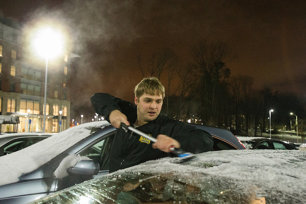George Mason forward, Scott Bangert, scraps off ice from his car before leaving for practice on George Mason University Fairfax campus on January 22, 2014.