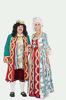 Portrait of senior couple as king and queen over gray background