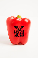 Close-up of red bell pepper with bar code over white background