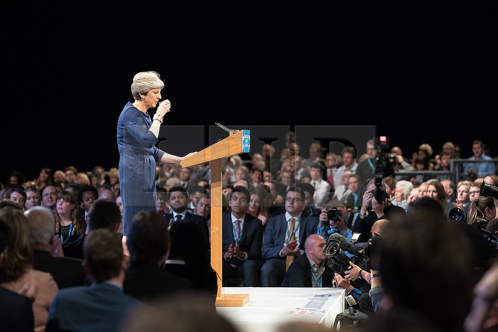 © Licensed to London News Pictures . 04/10/2017. Manchester, UK. Prime Minister THERESA MAY sips from a glass of water as she struggles with her voice and throat while she delivers her keynote speech on the fourth and final day of the Conservative Party Conference at the Manchester Central Convention Centre . Photo credit: Joel Goodman/LNP