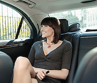 Mid adult woman at back seat of car looking out window