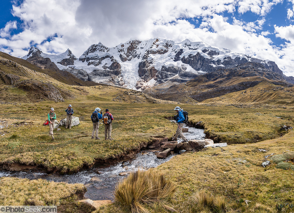Trekkers cross a stream under Nevado Carnicero (19,500 ft or 5960 m) near Carnicero settlement in the Cordillera Huayhuash, Andes Mountains, Peru, South America. Day 3 of 9 days trekking around the Cordillera Huayhuash. This panorama was stitched from 3 overlapping photos.