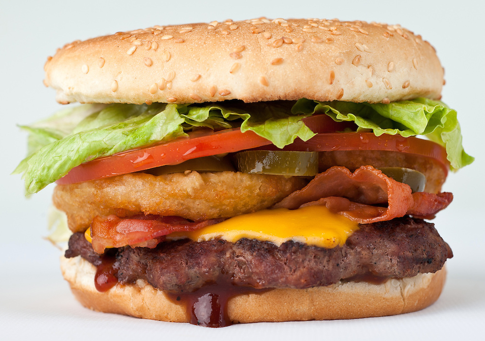 Photo of the Western Burger served at Dezereta Inc. in southern Utah area. Western burger contains, hamburger, BBQ sauce, hamburger, cheese, onion rings, bacon, lettuce, tomato, buns.