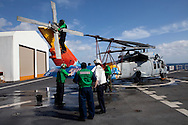 HSC 28, a helicopter sea combat detachment out of Norfolk, Virginia, preps an MH-60S helicopter to transport patients on the flight deck of the USNS Comfort, a naval hospital ship, as the ship makes its way to help survivors of the earthquake in Haiti on Monday, January 18, 2010 in the Atlantic Ocean off the coast of the United States.