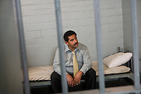 Criminal sitting on bed in jail