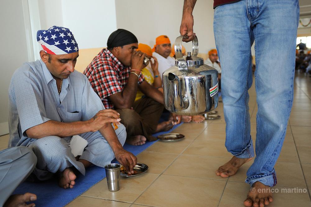 """Pessina Cremonese. Fedeli sikh si rifocillano al pianterreno. L'istituzione del """"Langar"""" (cucina comune) serve a creare uguaglianza sociale. La religione sikh prescrive che i fedeli hanno sempre diritto a essere nutriti."""