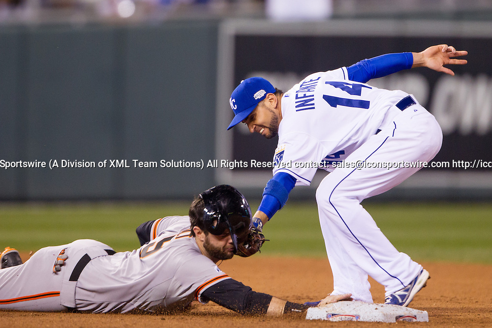 October 22, 2014: San Francisco Giants first baseman Brandon Belt (9) is tagged out in the face by Kansas City Royals second baseman Omar Infante (14) while diving back to second base during the MLB World Series Game 2 between the San Francisco Giants and the Kansas City Royals at Kauffman Stadium in Kansas City, Missouri.  The Giants lead the series 1-0.