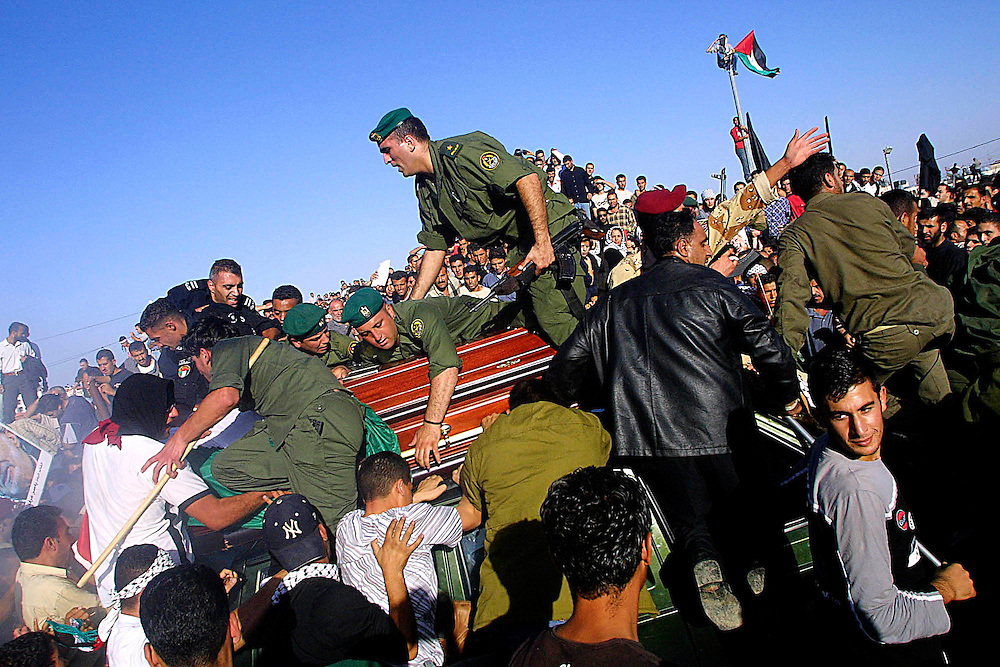 Palestinian soldiers escort the coffin of the late Palestinian leader Yassar Arafat, as mourners surge the Mukata compound in Ramallah in attempts to touch the coffin before the burial.  Friday Nov. 12, 2004.  To the roars of tens of thousands of Palestinians, and shots in the air fired by tense Palestinian police and masked gunmen, the flag-draped casket of Yasser Arafat was borne through milling, surging crowds Friday for burial in a plot next to the office to which Israel confined the Palestinian leader for nearly three years.  Photo by Olivier Fitoussi/BAUBAU