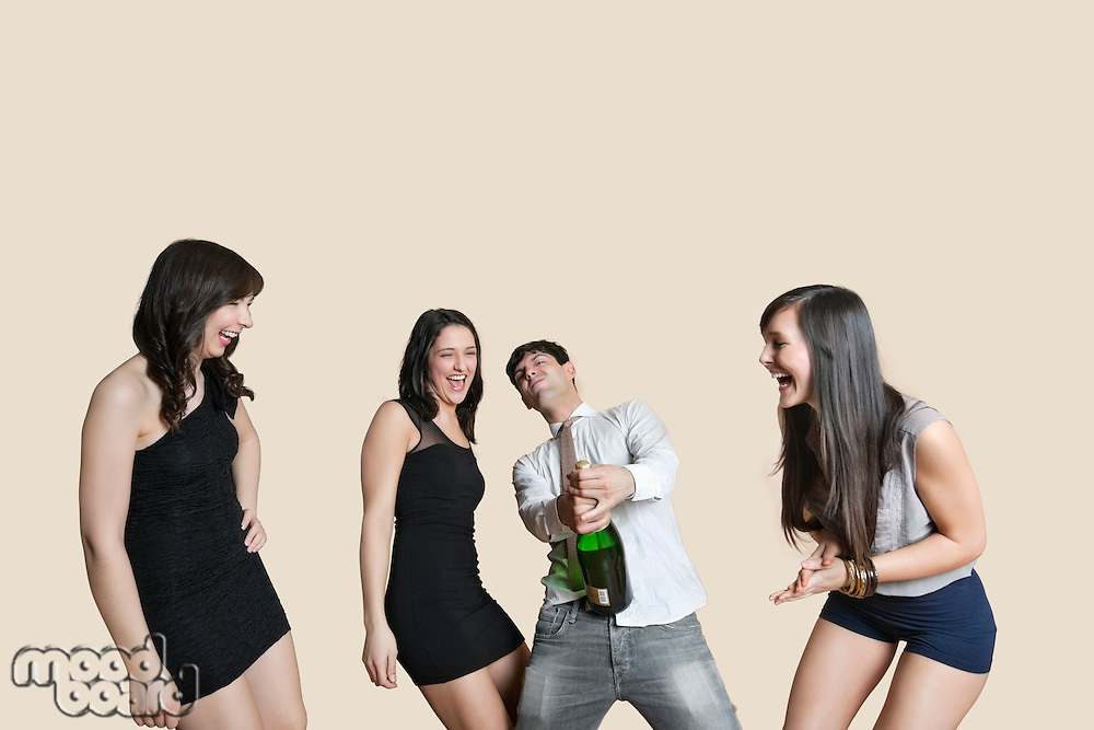 Cheerful young friends with champagne over colored background