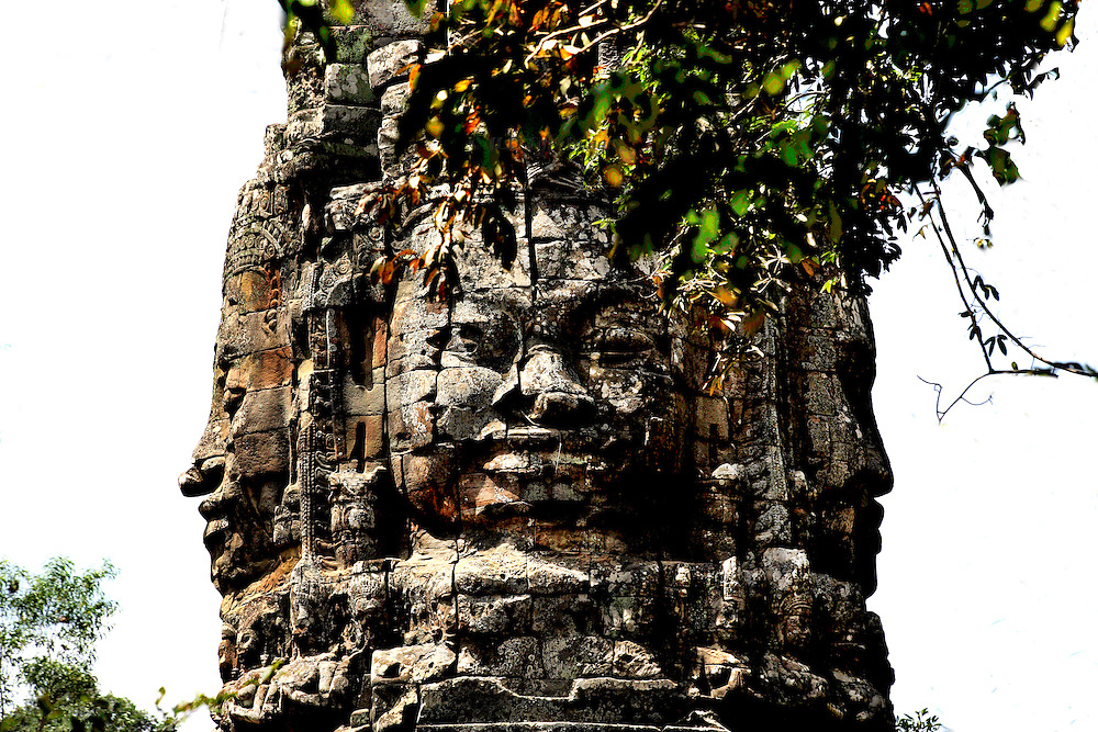 Detail of one facial portrait of a king; profiles of two others on either side. Festooned with leafy vines.  The sculpture sits on top of a gopura, or gate, to a temple precinct.  The figure faces in all four cardinal directionsin indicating protection all around.