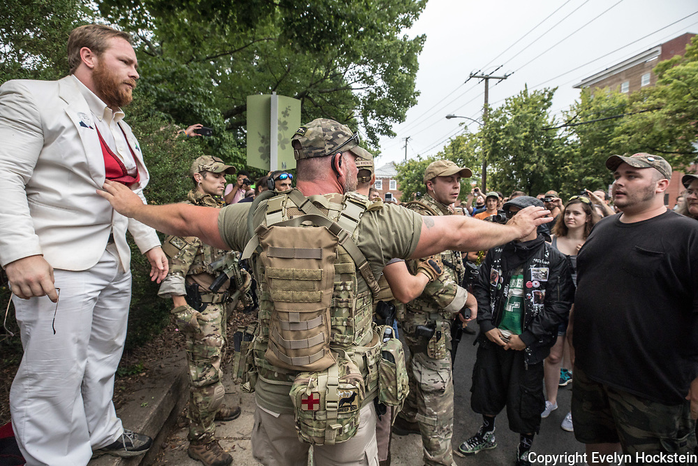 "CHARLOTTESVILLE,VA-AUG12: White supremacist groups and counter protestors argue while a member of ""The Militia"" keeps the peace outside the Unite the Right rally August 12, 2017. (Photo by Evelyn Hockstein/For The Washington Post)"
