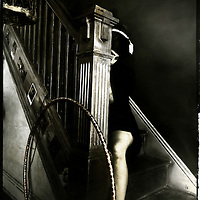 A woman sitting on the stairs with a hula hoop resting against the balustrade