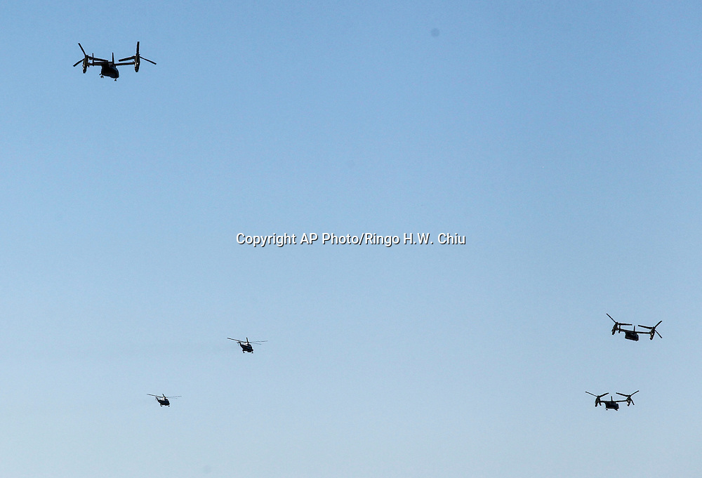 "Marine One, bottom 2nd left, with President Barack Obama aboard, and another Marine's helicopter, bottom left, are escorted by  ""Osprey"" aircrafts depart from Los Angeles International Airport in Los Angeles on Saturday, Oct. 10, 2015. (AP Photo/Ringo H.W. Chiu)"