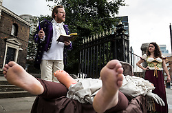 © Licensed to London News Pictures. 04/09/2015. London, UK. An actor dressed as author Daniel Defoe (left) reads an extract from his from 'A Journal of the Plague Year' outside St Boltoph without Aldgate Church. Actors in traditional costumes took part in a procession from Minories (near the Tower of London) to St Botolph's in which they dragged a cart with 'plague victims' and yelled 'bring out your dead' to passing members of public. This is to mark 350 years since the plague pit at church was completed. It also marks the opening of the Great Plague Festival which runs until September 6th. Photo credit : James Gourley/LNP