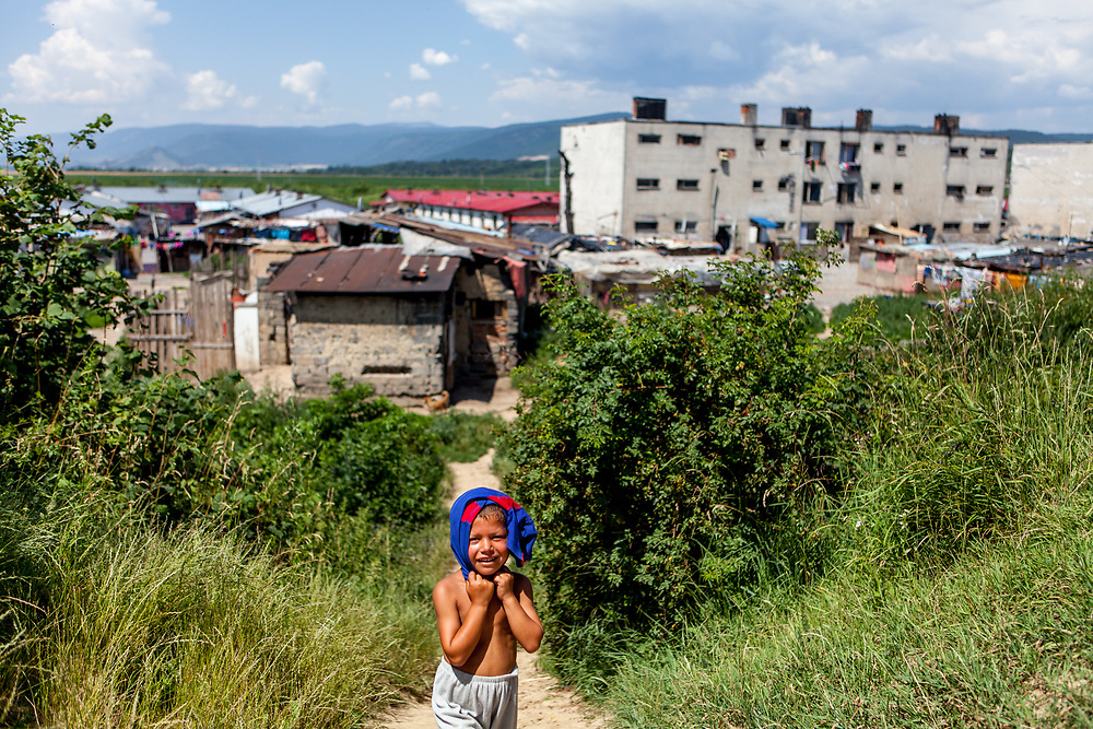 A boy covering his head with his T-Shirt during tropical temperatures at the Roma settlement 'Budulovska Street' in Moldava nad Bodvou. From about 800 inhabitants of the segregated settlement 'Budulovska Street' (2014) are roughly 392 children up to the age of 16 years.