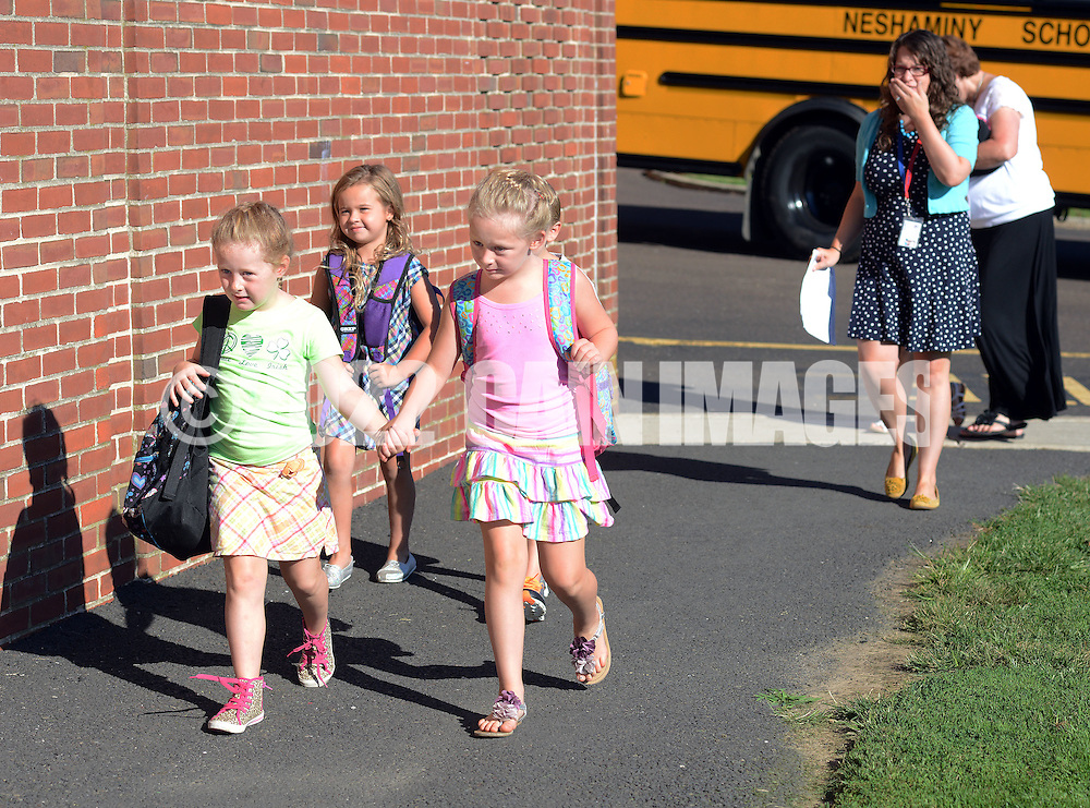 LOWER SOUTHAMPTON, PA - AUGUST 28:   Delia Carra (L), 5 and her sister Ruby Carra (R), 6 hold hands as they walk together into the building at the start of the first full day of school at Lower Southampton Elementary School August 28, 2014 in Lower Southampton, Pennsylvania.  (Photo by William Thomas Cain/Cain Images)