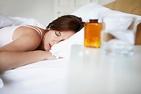 Sick woman in bed by pills on bedside table