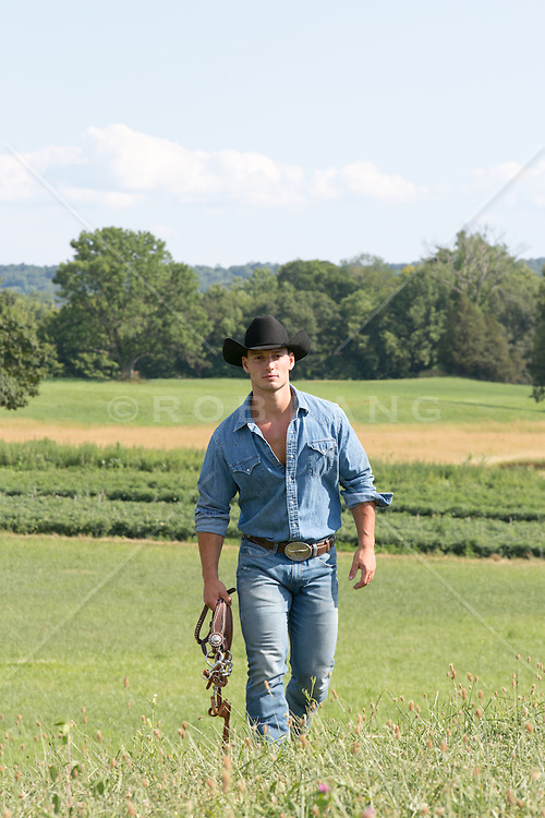 cowboy walking through a pasture on a ranch