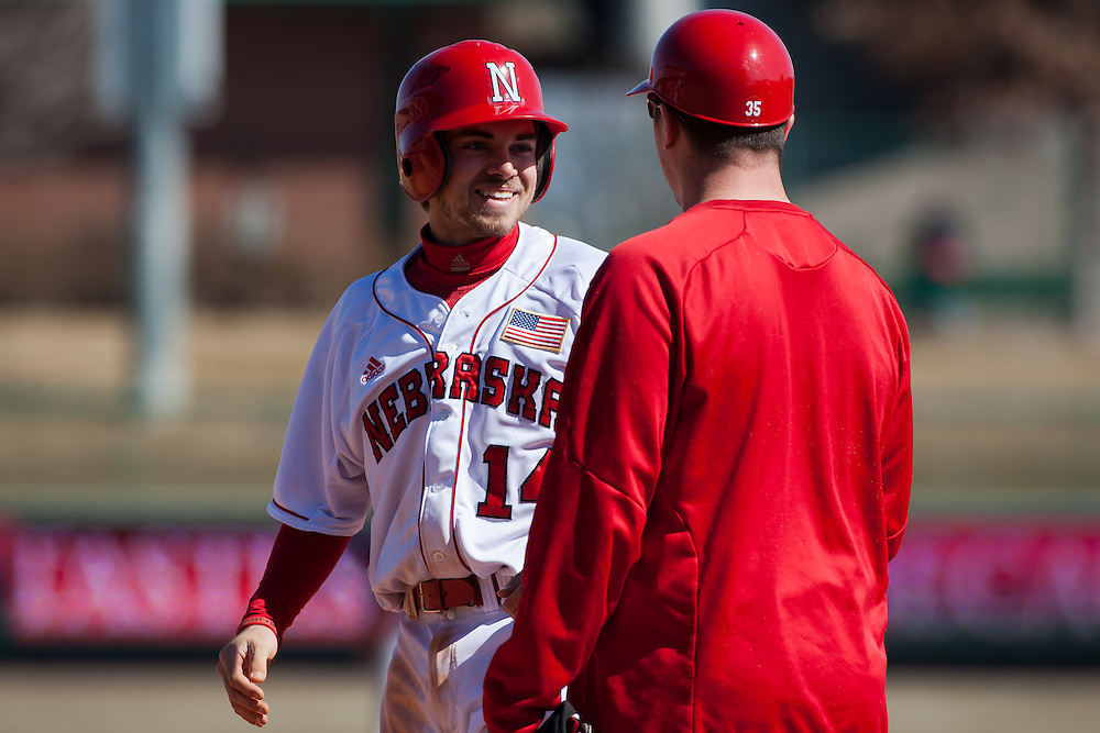 March 06, 2013: Nebraska's Wes Edrington #14 reached first base and is talking to first base coach Jeff Christy at Haymarket Park in Lincoln, Nebraska. Nebraska defeated Northern Colorado 10 to 5 in the first game of a double header.