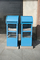Blue newspaper dispensers on sidewalk; Tallinn; Estonia; Europe