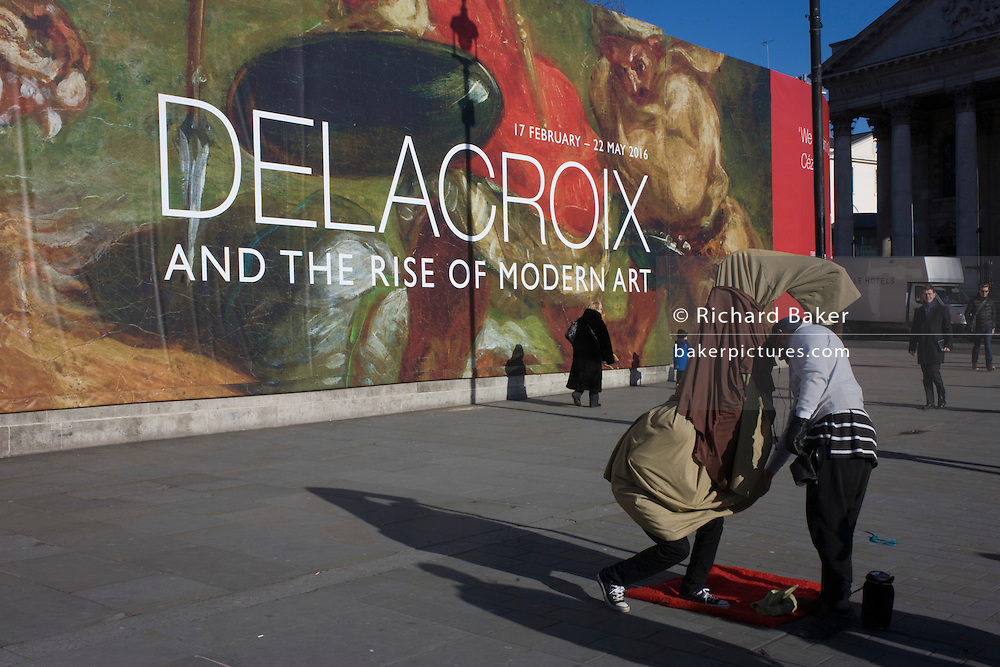 A busker dressed as Yoda stands in front of the broad message on a hoarding announcing the next major exhibition by Delacroix at the National Gallery in London.