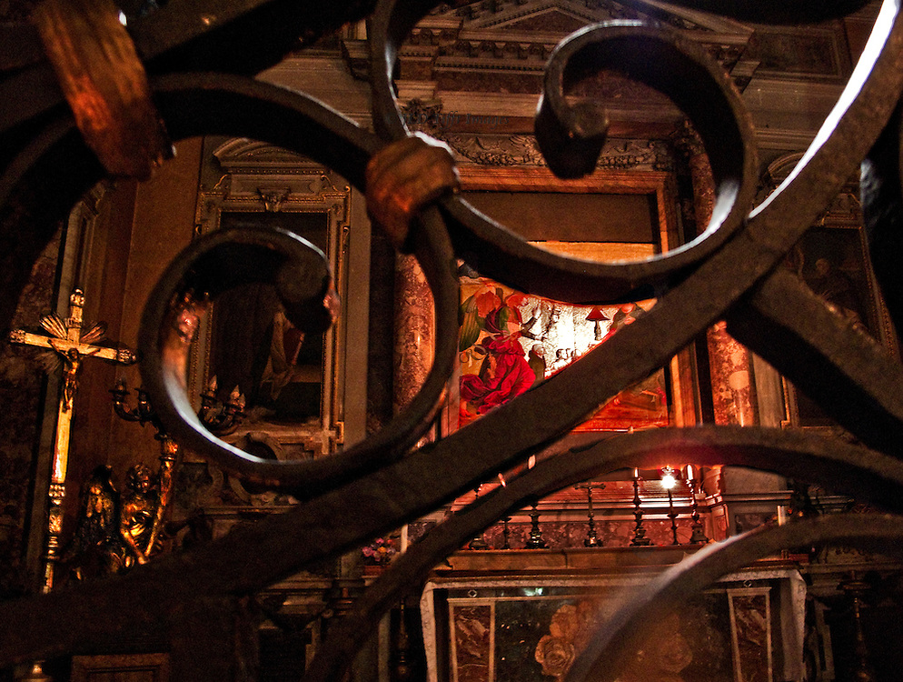 View through wrought iron gate into a chapel with Annunciation altarpiece, in Santa Maria sopra Minerva. Rome.  I am not a Catholic and the metal barrier represents my incomprehension of that belief system.