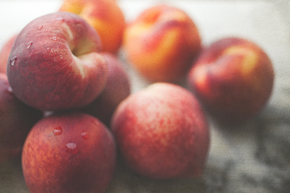 A still life image of a bunch of very ripe and juicy peaches on a marble slab.  Bright orange and yellow colors stand out against the monotone marble surface. Rustic modern yet simplistic and a lovely addition to any kitchen or dining area. Photographed in my studio.