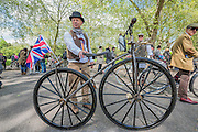 A very old bike with wooden spokes and solid tyres - The Tweed Run, a very British public bicycle ride through London's streets, with a prerequisite that participants are dressed in their best tweed cycling attire. Now in it's 8th year the ride follows a circular route from Clerkenwell via the Albert Memorial, Buckinham Palace and Westminster.