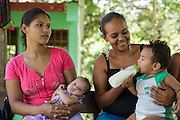 A woman feeds her son while waiting to have him vaccinated during a vaccination session at the primary school in the town of Coyolito, Honduras on Wednesday April 24, 2013.