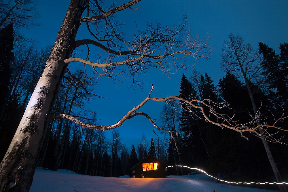 Illuminated tree and headlamp trail at night outside the backcountry North Pole Hut, San Juan Mountains, Colorado.