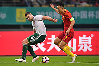 Feng Xiaoting, right, of Chinese national men's football team kicks the ball to make a pass against Sam Vokes of Wales national football team in the semi-final match during the 2018 Gree China Cup International Football Championship in Nanning city, south China's Guangxi Zhuang Autonomous Region, 22 March 2018.