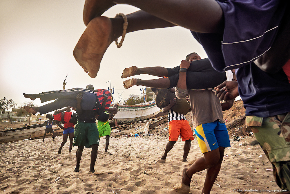 Young wrestlers train at the school of ex-Wrestler Boy Kaire at the Corniche in Dakar on April 3, 2015. Many young men dream of a career as a Wrestler like Kherou Ngor made it. Because they do not have a lot of money, they mostly train with the easiest instruments. Here the wrestling trainees have to run through the sand, carrying each other.