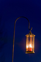 A shepherd's hook and hanging lantern create a warm glow remniscent of the Christmas season.