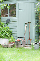 Gardening tools lean against door of potting shed