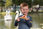 A young man enjoys a slice of pizza at the State Fair of Texas.