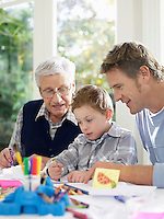 Boy (3-4) drawing with crayons with father and grandfather in house
