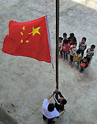 QIANNAN, CHINA - MAY 31: (CHINA OUT) <br /> <br /> Six-pupil School In Mountain Of Qiannan<br /> <br /> The only teacher Wu Guoxian and pupils hold a flag-rising ceremony at Gugang primary school in a mountain in Longli County on May 31, 2016 in Qiannan Buyei and Miao Autonomous Prefecture, Guizhou Province of China. Gugang primary school with only one teacher and six students was located in the mountain where the traffic was blocked in Qiannan. 50-year-old Wu Guoxian had been teaching in this school for 33 years and taught over 1,000 students. More and more people went out of the village to work in the cities leaving their children and the old in the mountain. Five under-school-age kids whose parents left for work also stayed at the school. <br /> ©Exclusivepix Media