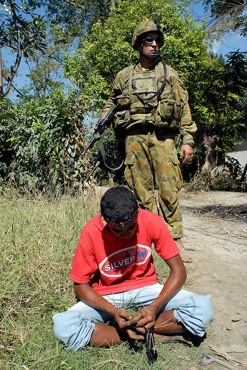 Australian soldiers patrol the Comora area of Dili, a hot point for clashes between rival gangs, the ( Lorosae) and the Westerners (Loromonu). This young man was suspected of acting as a sentry, tipping off members of his gang as to the whereabouts of the peacekeepers. 05/06/06