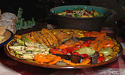 A plate of grilled vegetables, peppers, sweet potato and eggplant garnished with herbs