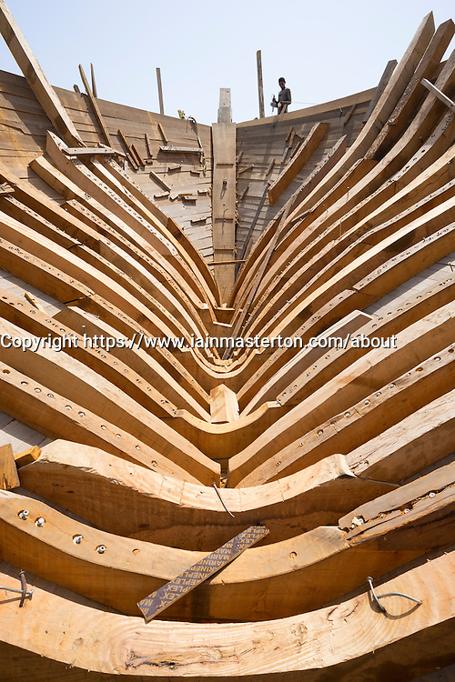 detail of keel construction of a  traditional wooden dhow cargo ship being built in shipyard beside The Creek River in Dubai United Arab Emirates