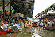 Floating Markets of Southeast Asia<br /> <br /> Floating markets, where goods are sold from boats, are a trademark attraction among the Southeast Asian countries such as Thailand, Indonesia and Vietnam. They originate from a time when water transport played an important role in daily life.<br /> All these countries are located either on islands or on wet lowlands with broad river valleys. Located in tropical climate, this region was thick jungles prior to human development. The first places to be settled were adjacent to the rivers, and the people living there used boats as their main mode of travel rather than trying to push their way through the dense jungle. Although the region is now developed and there is a network of roads connecting all cities and towns, boats are still used for transport and trade by the communities along the waterways, especially by farmers whose farmlands are located by the riverside.<br /> <br /> Farmers bring their produces in boats to the markets and sell them to local dealers directly from the boats, eliminating the need to setup shops in the docks. That way they could quickly sell their products and return back to their home. The local dealers buy the products and sell them to shops in the neighboring towns and to wholesale dealers from the big towns. Floating markets are also a big tourist draw.<br /> The most famous floating market, and a tourist haven, is the one in Damnoen Saduak about 100km southwest of Bangkok. The floating market is crowded with hundreds of vendors and purchasers floating in their small boats selling and buying agricultural products and local food. The market opens in the early morning and closes about an hour before noon.<br /> Amphawa floating market, located in Amphawa district, about 72 km from Bangkok, is not as large as Damnoen Saduak floating market but it is more authentic, with visitors almost exclusively Thais. It is an evening floating market but some stalls are opened at noon too. Other floating mar