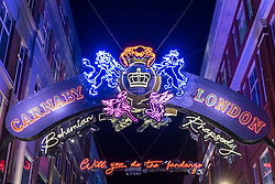"© Licensed to London News Pictures. 24/10/2018. LONDON, UK.  Tourists and shoppers enjoy viewing the Christmas lights in Carnaby Street.  This year, the lights are in the form of the lyrics to Queen's Bohemian Rhapsody to coincide with the release of the movie ""Bohemian Rhapsody"", which is opens in UK cinemas today.  Photo credit: Stephen Chung/LNP"