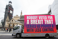 London, UK. 14th January, 2019. An advertising truck commissioned by the People's Vote campaign passes in front of the Houses of Parliament.