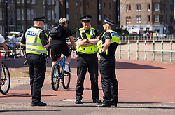 Portobello, Scotland, UK. 8 May 2020. Images from Friday afternoon during Covid-19 lockdown on promenade at Portobello. Promenade and beach were busier than in recent weeks due to warm sunny weather and the fact that several cafes and takeaway food shops are now open. Police patrols were low key. Pictured; Police patrol the promenade. Iain Masterton/Alamy Live News