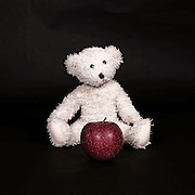 a white teddy bear and a red apple