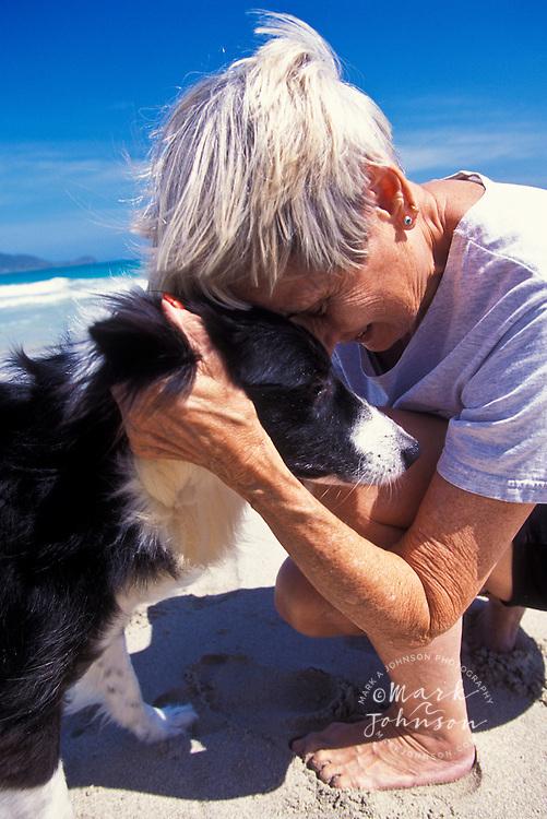 Mature age woman cuddling pet dog on beach, Kailua, Oahu, Hawaii