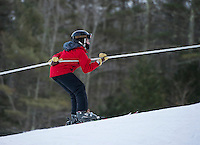 With a strong grip and some duct tape Rob Doherty takes a quick ride up the rope tow at the Abenaki Ski Area in Wolfeboro.  (Karen Bobotas/for the Laconia Daily Sun)